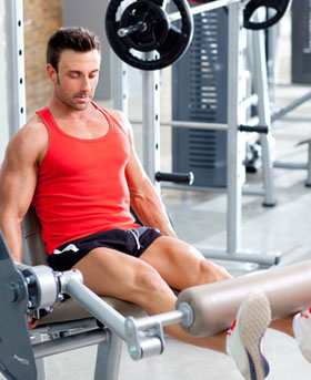 man on leg extension weight machine