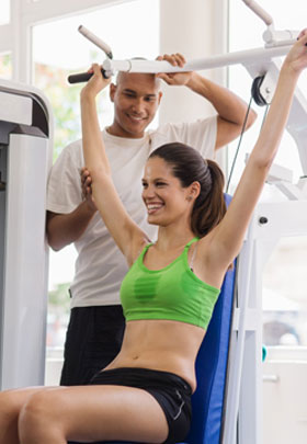 woman and trainer on leased fitness equipment